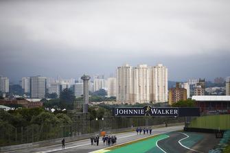 Lo skiline di San Paulo dietro a Pierre Gasly, Toro Rosso, e i membri del suo team, che, ispezionano il circuito accanto a Sergio Perez, Force India