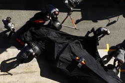 Mecánicos de McLaren empujan el cubierto coche de Stoffel Vandoorne McLaren MCL32 en su garaje después de que encontró un problema técnico en la pista