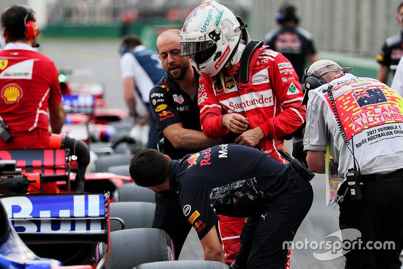 Гонщик Ferrari Себастьян Феттель пытается осмотреть Red Bull Racing RB13