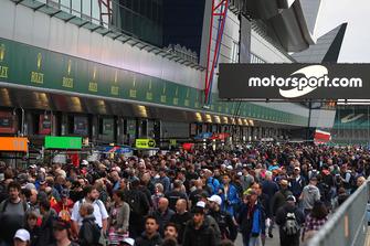 Les fans dans la voie des stands avec les logos Motorsport.com