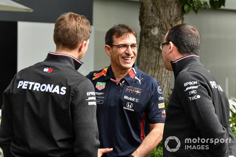 Mercedes and Red Bull personnel talk in the paddock