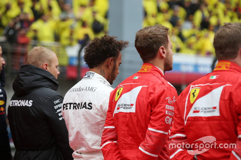 Valtteri Bottas, Mercedes AMG, Lewis Hamilton, Mercedes AMG, Sebastian Vettel, Ferrari, and Kimi Raikkonen, Ferrari, join the other drivers on the grid for the national anthem