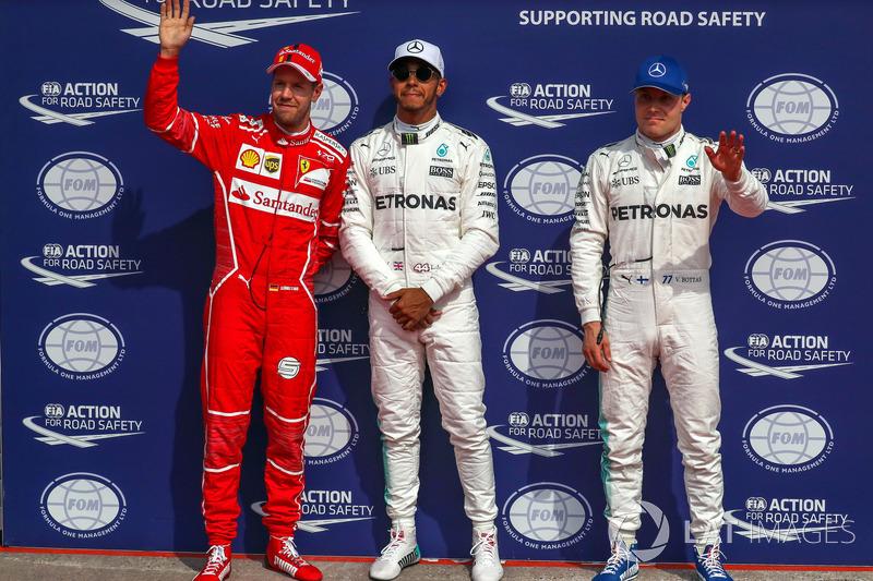 Polesitter Lewis Hamilton, Mercedes AMG F1 celebrates in parc ferme alongside Sebastian Vettel, Ferr