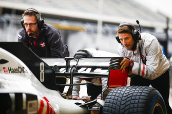 Romain Grosjean, Haas F1 Team, helps to push his car during pit stop practice.