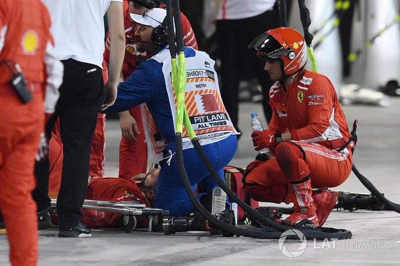Un mecánico de Ferrari es atendido por médicos después de ser golpeado por el coche de Kimi Raikkonen, Ferrari SF71H durante una parada en boxes