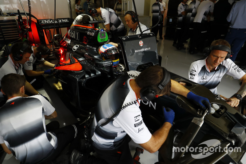 McLaren personnel work on Fernando Alonso's MP4-31 Honda in the garage