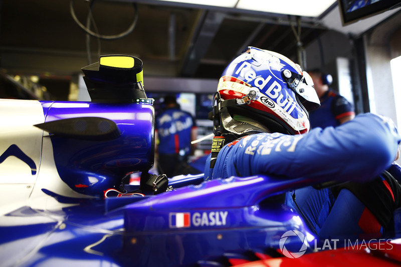 Pierre Gasly, Toro Rosso, enters his cockpit in the team's garage.