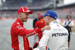 Sebastian Vettel, Ferrari, celebrates his pole position, with Valtteri Bottas, Mercedes AMG F1