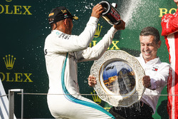 Lewis Hamilton, Mercedes AMG F1, 1st position, sprays his team mate with Champagne, who in turn defends himself from the spray with the Constructors trophy