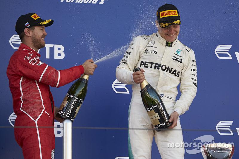 Second place Sebastian Vettel, Ferrari, sprays Race winner Valtteri Bottas, Mercedes AMG F1