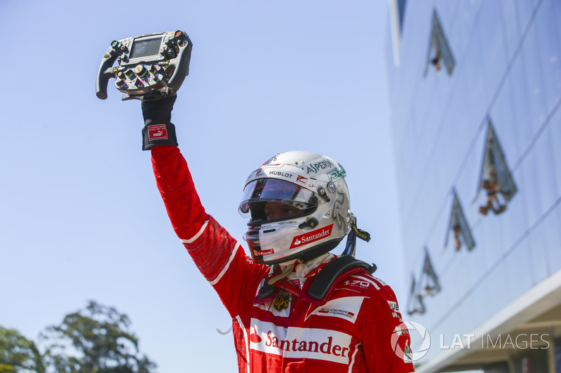 El ganador de la carrera de Brasil, Sebastian Vettel, Ferrari, sujeta el volante de su coche