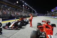 Гонщик Ferrari Себастьян Феттель осматривает автомобиль Red Bull