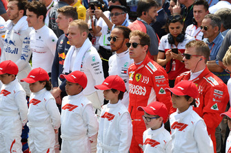 Piloti e grid kid osservano l'inno nazionale, in griglia di partenza