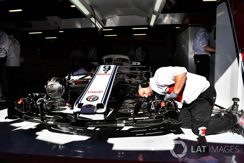 Механики Alfa Romeo Sauber работают над автомобилем C37 в гараже