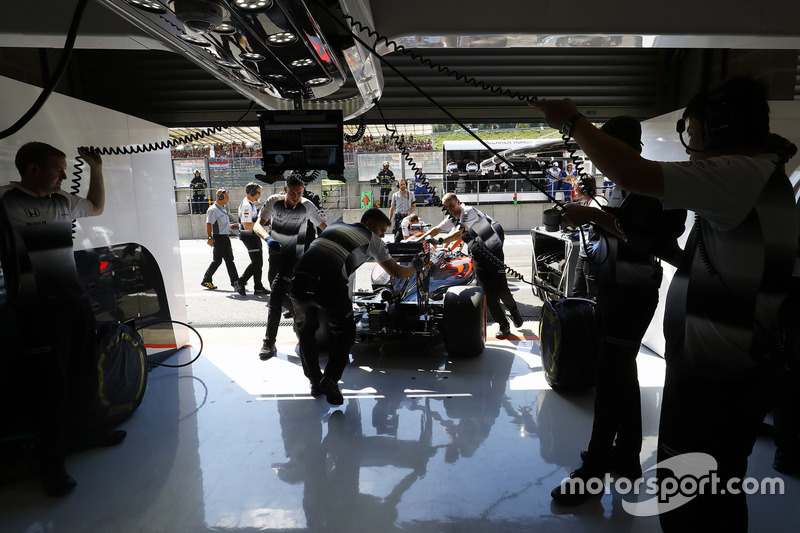 I membri del team spingono Jenson Button, McLaren nel box