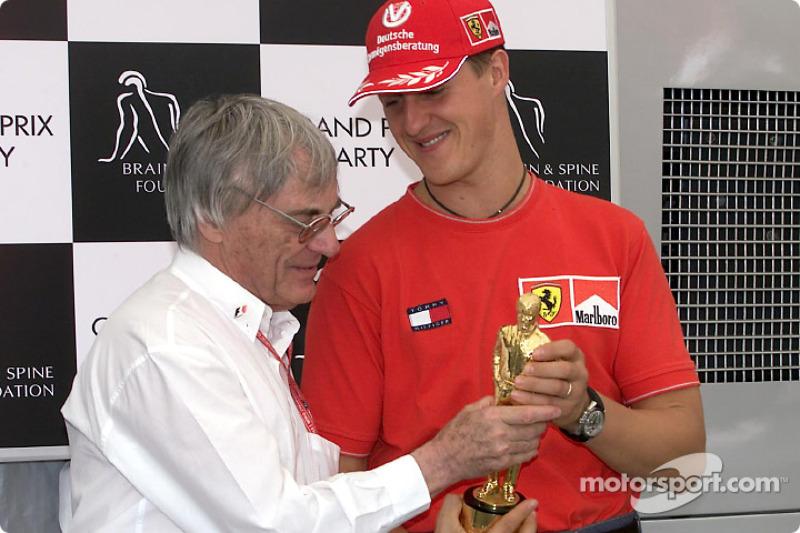 Michael Schumacher receive his 'Bernie' from Bernie Ecclestone
