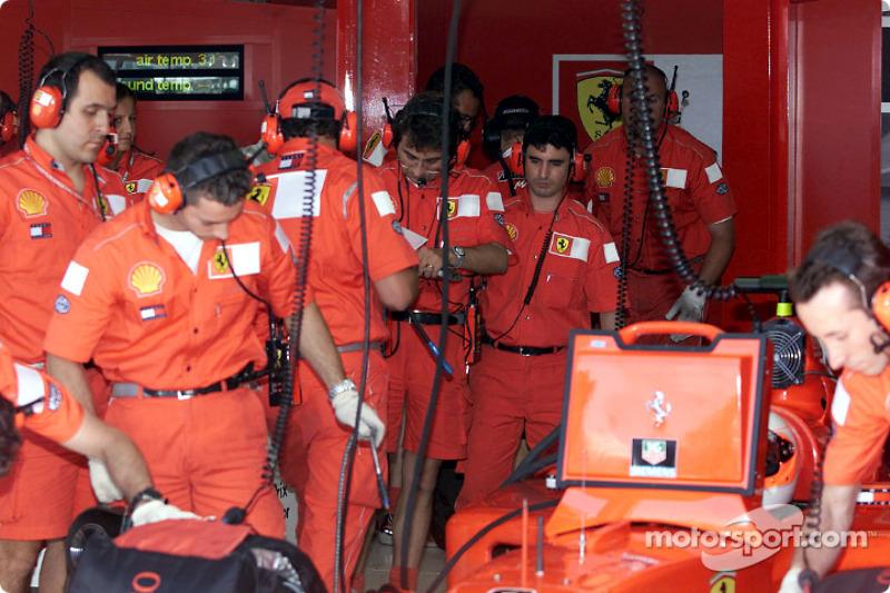 Team Ferrari working while Rubens Barrichello is waiting