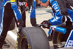 Cleaning off rubber buildup on tires off of Ryan Newman's Alltel Ford