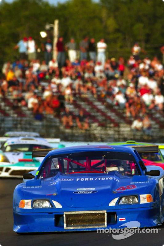 Fans regardent pendant que la #48 Mustang of Heritage Motorsports gagnante du AGT mène un groupe de voitures