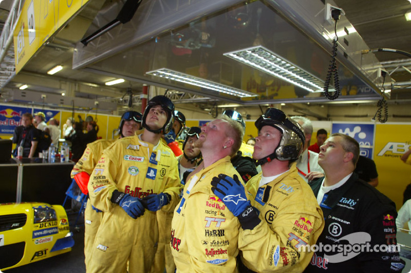 Abt crew members following the race in the garage