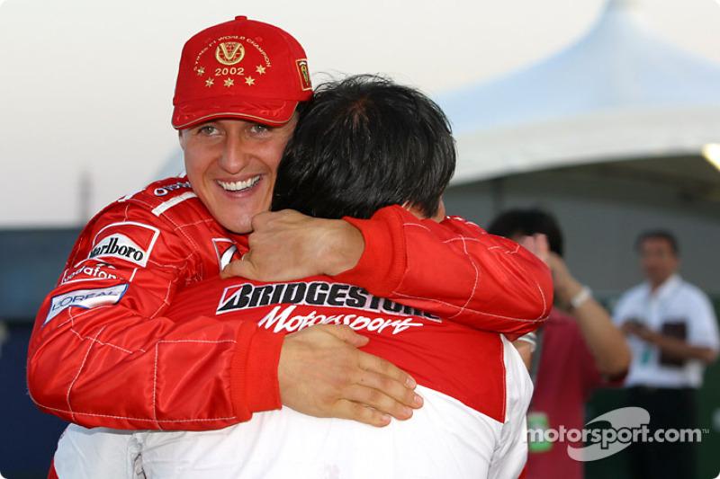Michael Schumacher celebra con un miembro del equipo de Bridgestone