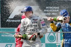 The podium: champagne for race winner Kimi Raikkonen, Rubens Barrichello and Fernando Alonso