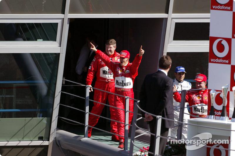 El ganador, Michael Schumacher y Ross Brawn celebran en su camino hacia el podium