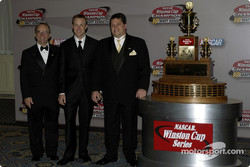 Matt Kenseth is joined by Jack Roush and Robbie Reiser for a photo with the trophy