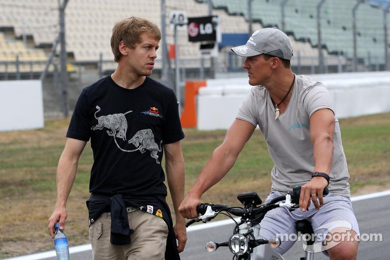Sebastian Vettel, Red Bull Racing wandelt op het circuit  en praat met Michael Schumacher, Mercedes GP