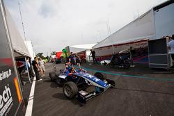 Een techneut van Carlin stuurt de auto van Josef Newgarden door de paddock