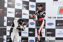 Race 1 winner Nicola de Marco and Will Bratt spray champagne on the podium