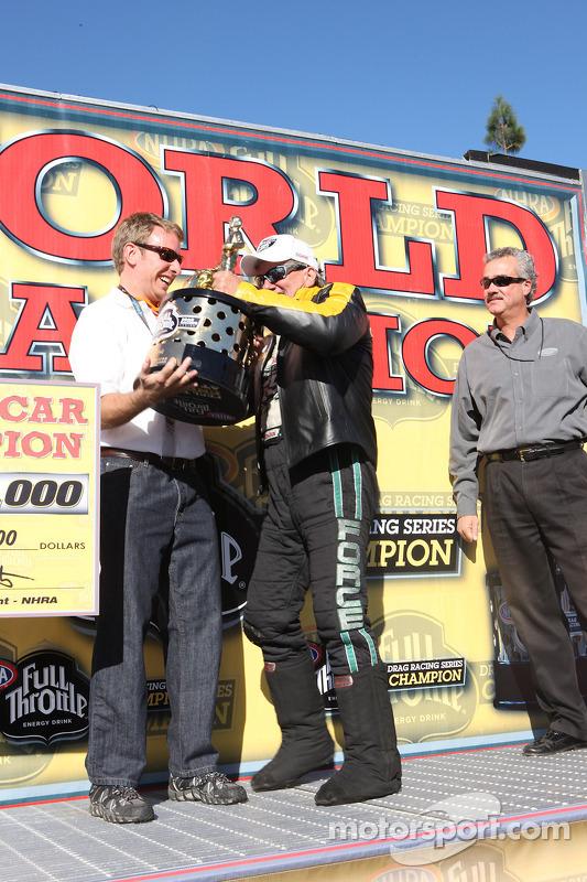 John Force geeft zijn funny car-wereldkampioenschapstrofee aan Henry Ford de derde