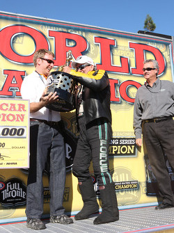 John Force giving his funny car world championship trophy to Henry Ford the third