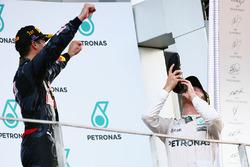 Третє місце Ніко Росберг, Mercedes AMG F1 святкує на подіумі і п'є шампанське із гоночного черевика переможця Даніеля Ріккардо, Red Bull Racing