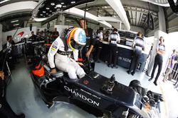 Fernando Alonso, McLaren MP4-31 climbs into his car in the garage.