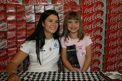 Danica Patrick poses for a picture with a young fan