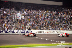Dan Wheldon takes the checkered flag in front of Helio Castroneves