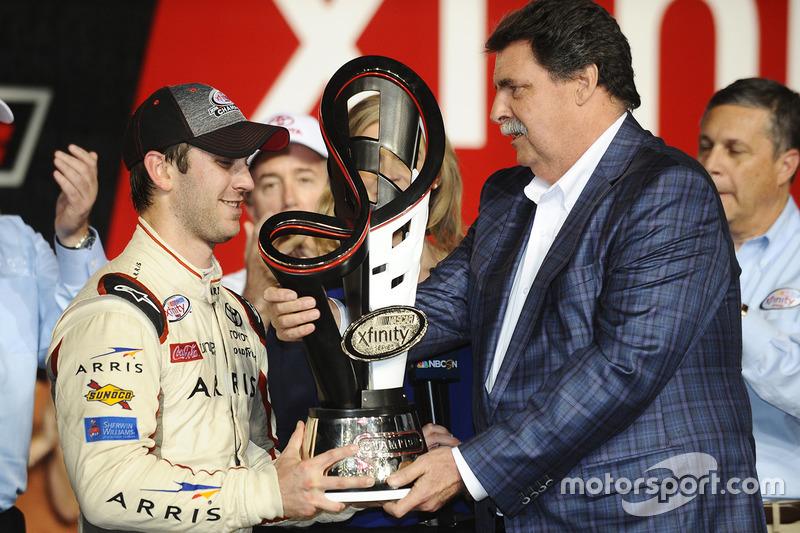 Ganador de la carrera y Campeón 2016 Daniel Suárez, Joe Gibbs Racing Toyota, NASCAR presidente Mike Helton con el trofeo del campeonato de Xfinity Series