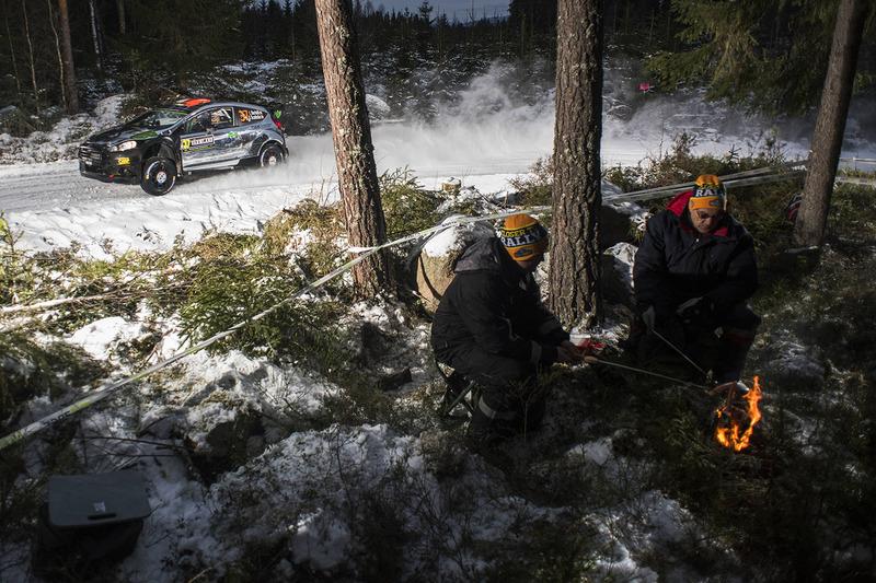 Fans maken een vuurtje, Lorenzo Bertelli passeert in de Ford Fiesta RS WRC