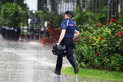 A Sky Sports F1 Cameraman gets caught in the rain in the paddock