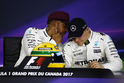 Lewis Hamilton, Mercedes AMG F1, shows off his Ayrton Senna helmet, a gift after equalling the Brazilian's pole record, alongside Valtteri Bottas, Mercedes AMG F1, in the post-qualifying press conference