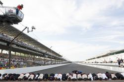 Brad Keselowski and his Penske Racing team members kiss the yard of bricks