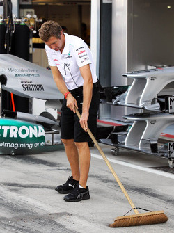 Mercedes AMG F1 mechanic sweeps the pit lane