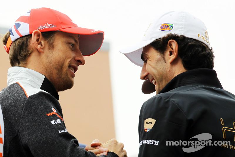 Jenson Button, McLaren met Pedro De La Rosa, HRT Formula 1 Team rijdersparade