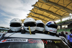 An entire team's stable of drivers' helmets adorn the roof of a car prior to the start of the Sepang 1000km 2012.