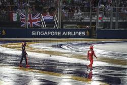 Гонщик Red Bull Racing Макс Ферстаппен и пилот Ferrari Кими Райкконен возвращаются в боксы после аварии
