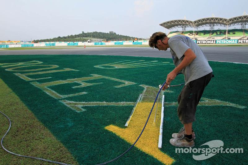 Een medewerker verft het gras