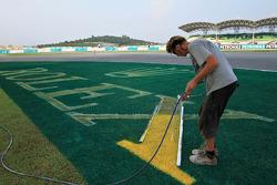 Um trabalhador pinta a grama