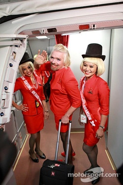 Sir Richard Branson serves as a flight attendent on Air Asia flight after losing a bet with Caterham F1 boss Tony Fernandes