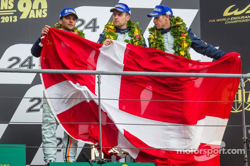 LMGTE Pro podium: third place Darren Turner, Stefan Mücke, Peter Dumbreck with a Danish flag for Allan Simonsen
